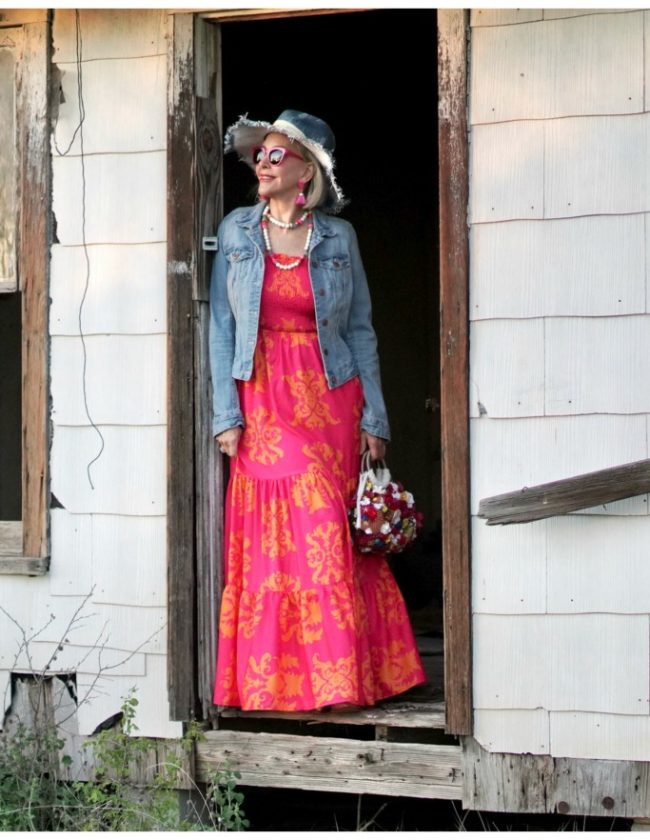 Sheree Frede of the SheShe Who standing in an abandoned house wearing an orange and pink maxi dress with denim jacket