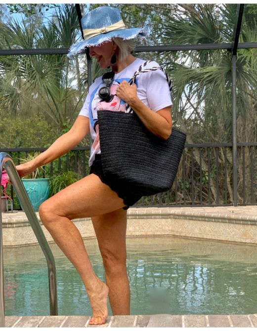 Sheree Frede stepping into swimming pool wearing shorts and hat