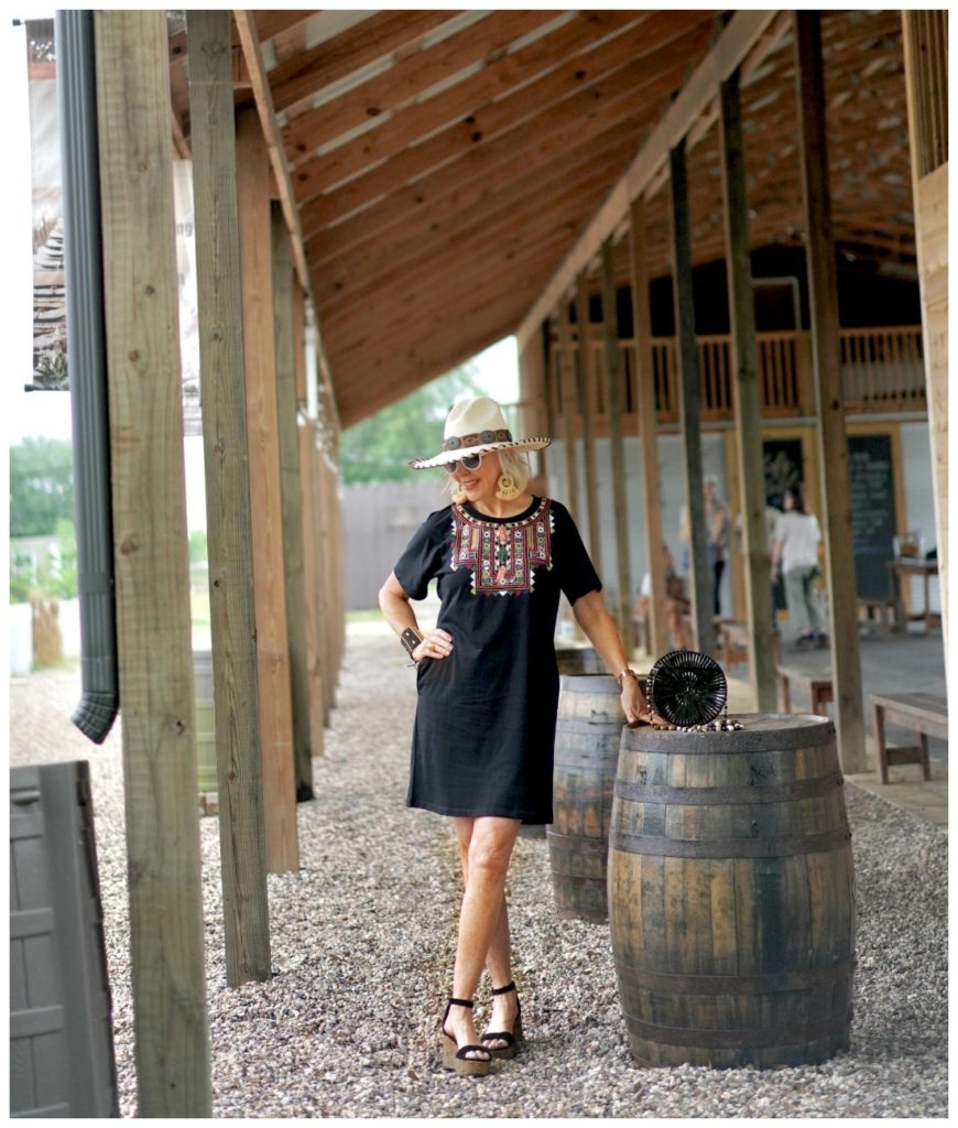 Sheree Frede of the SheShe Show standing under a shed by a barrel wearing a black shirt dress and hat