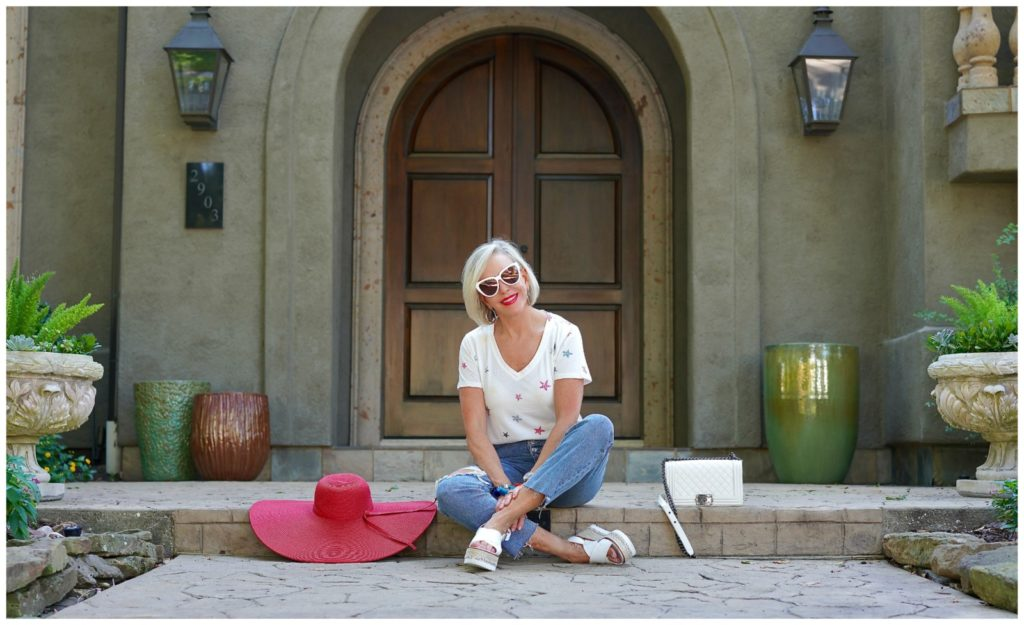 sheree of the SheSheShow sitting in front of house wearing ripped jeans and white star tee shirt