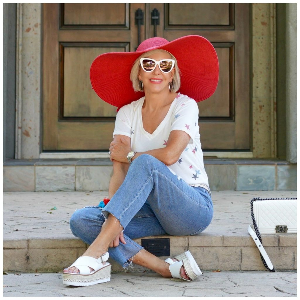 sheree of the SheSheShow sitting in front of house wearing ripped jeans and white star tee shirt and red hat