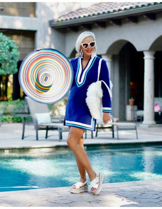 Sheree Frede of the SheShe Show standing by swimming pool wearing a short navy swimsuit coverup with big strip sunhat and large white fringe tote bag