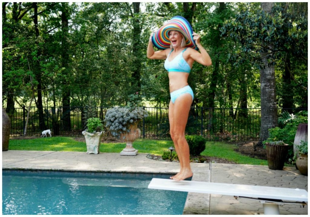 Sheree Frede of the SheShe Show on diving board  wearing an aqua 2 piece swimsuit
