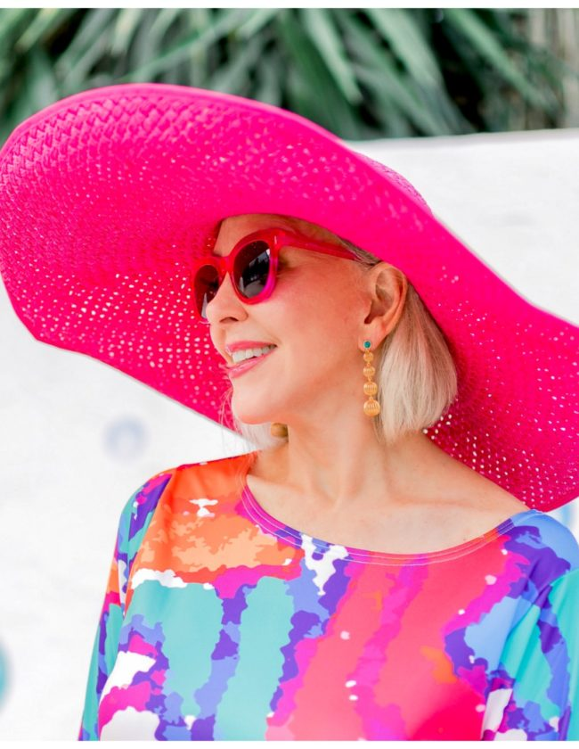 Sheree Frede of the SheShe Show wearing a big pink hat and colorful print dress