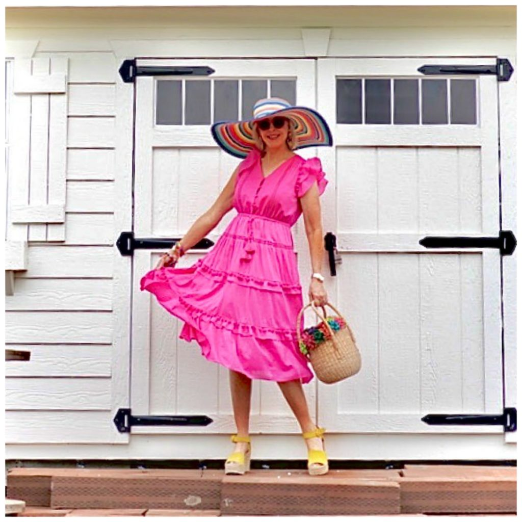 Sheree Frede of the SheShe Show standing in front of a white door wearing a hot pink dress and large hat