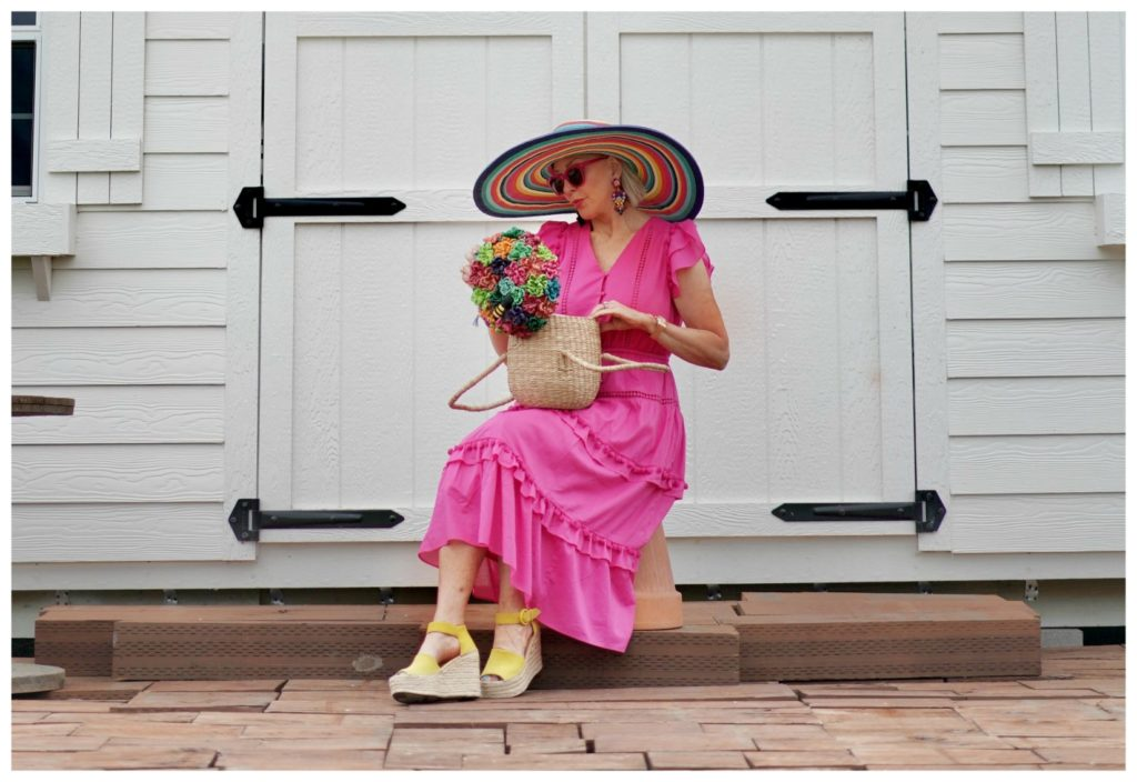 Sheree Frede of the SheShe Show sitting in front of a white door wearing a hot pink dress and large hat