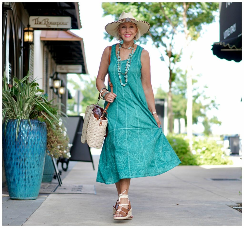Sheree Frede of the SheShe Show walking down alley wearing green dress carrying straw toter