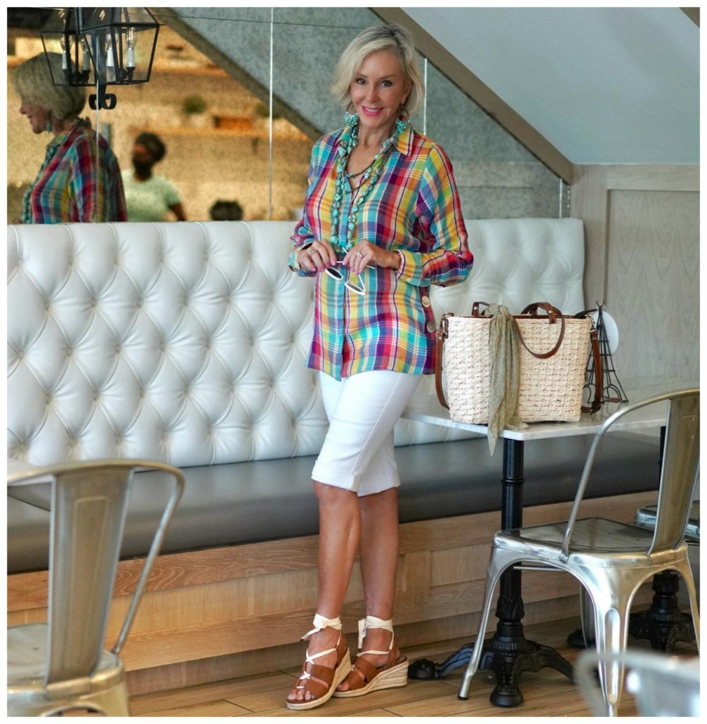Sheree Frede of the SheShe SHow standing in a restaurant wearing a plaid shirt, white shorts, straw bag.