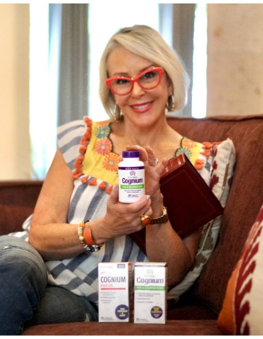 Sheree Frede of the SheShe Show sitting on sofa looking at photos with Natrol Memory supplements
