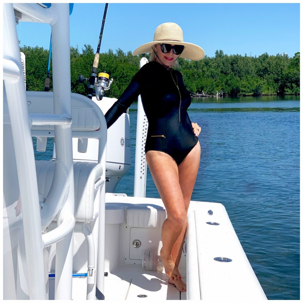 Sheree Frede of the SheShe Show on a small white boat wearing a black unisuit