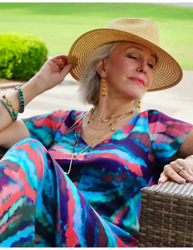 Sheree of the SheShe Show wearing multi colored dress with hat and layered necklaces
