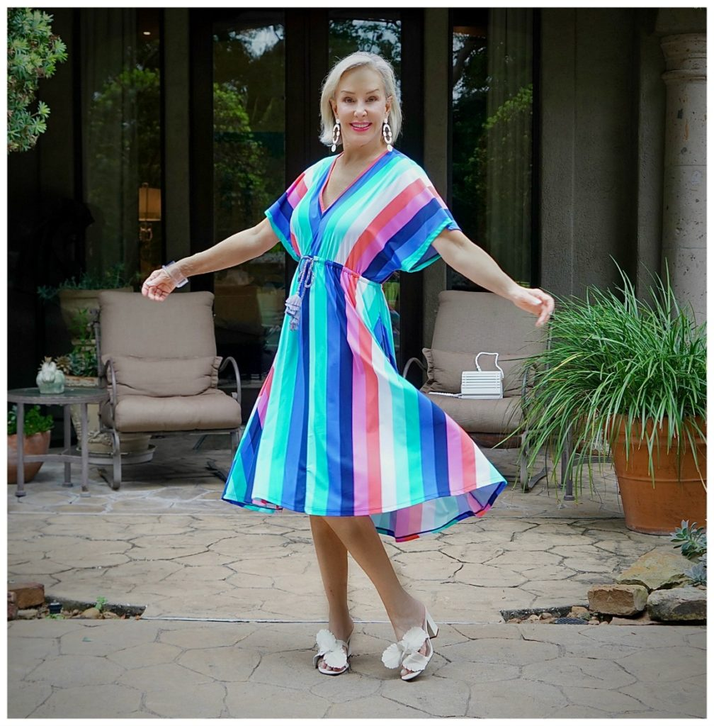 Sheree Frede of the SheShe Show twirling in a colorful stripe midi dress