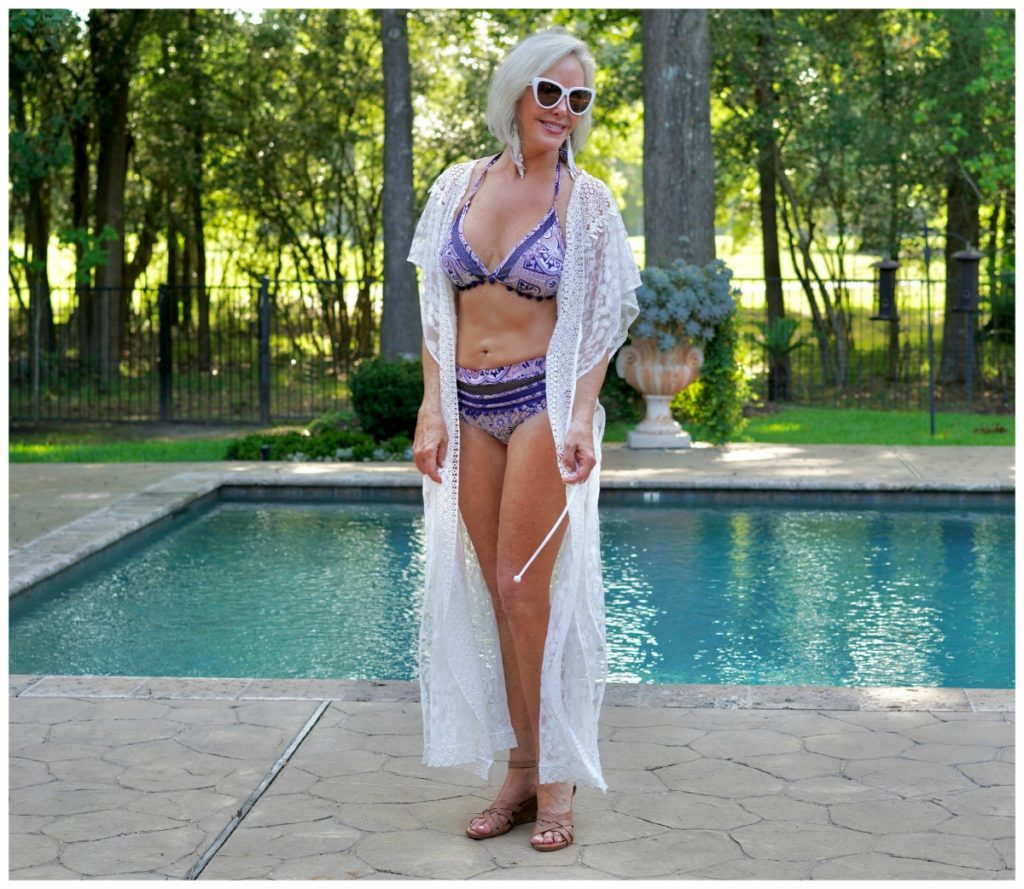Sheree Frede of the SheSheSHow by swimming pool wearing white long lace swimsuit coverup over 2 pc swimsuit
