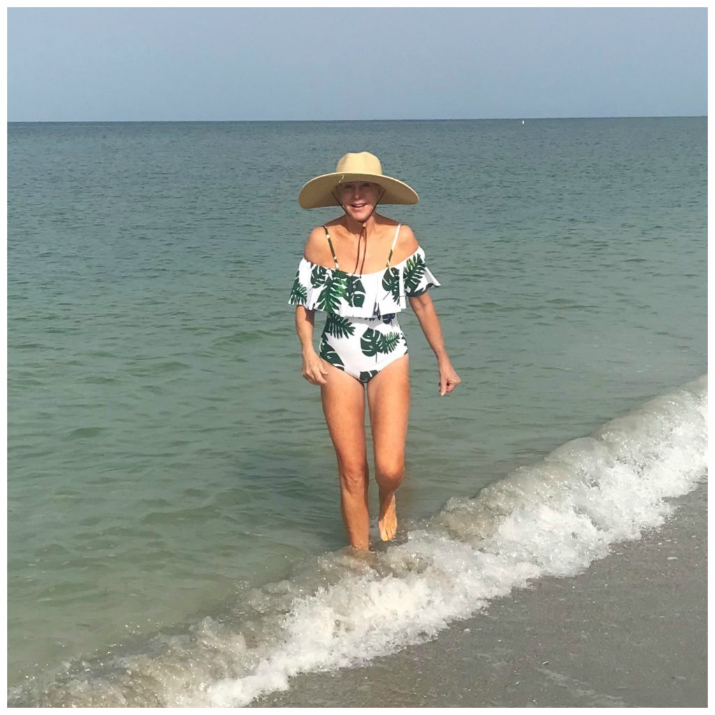 Sheree Frede of the SheSheShow wearing a tropical print off the shoulder swimsuit