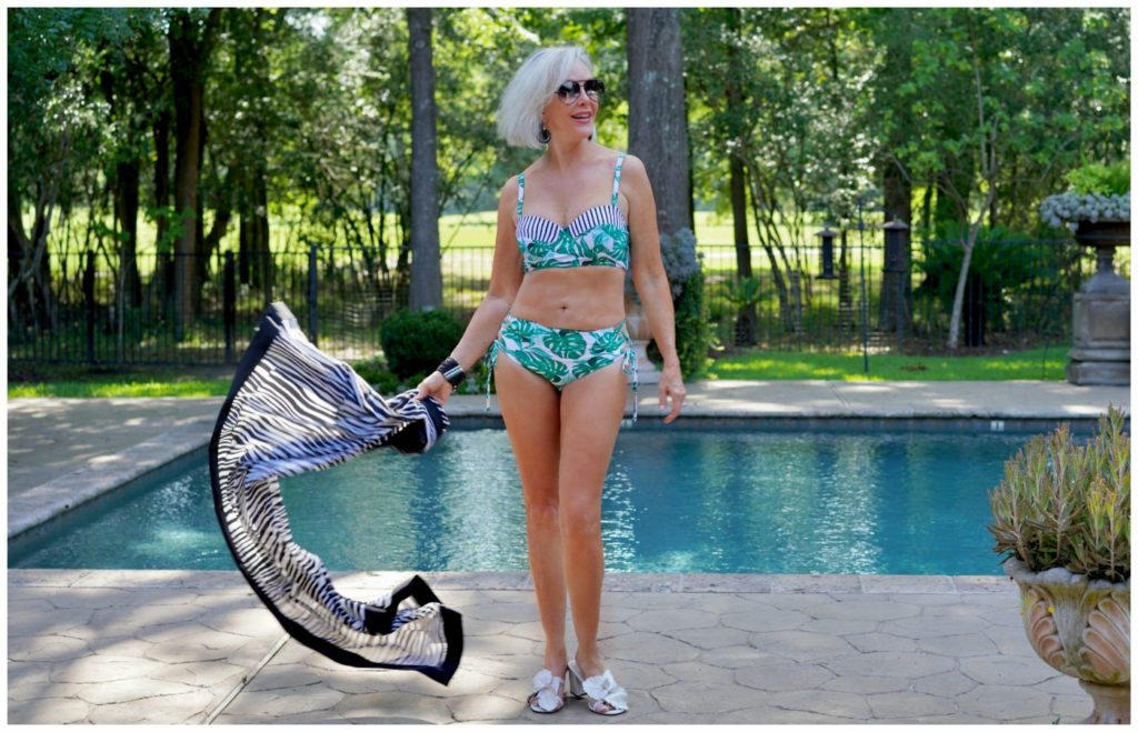 Sheree Frede of the SheSheSHow by swimming pool wearing a 2 piece tropical print swimsuit with black & white large scarf