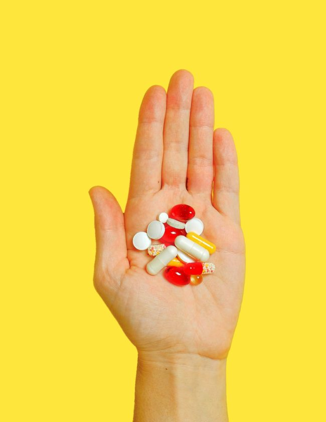 photo of a hand holding several vitamins