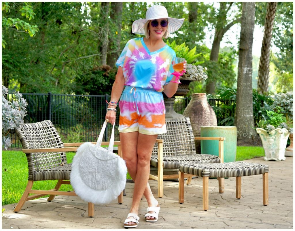 Sheree Frede of the SheShe Show out on patio wearing a 2 piece shorts and top tie dye set with large white fringy straw tote bag and big white hat