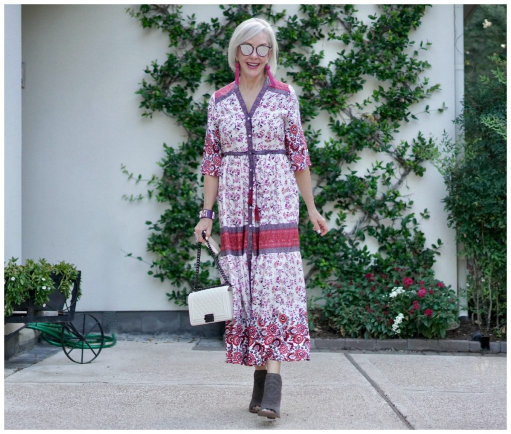 Sheree Frede of the SheSheShow standing in front of trellis wall wearing a maxi red and white floral dress