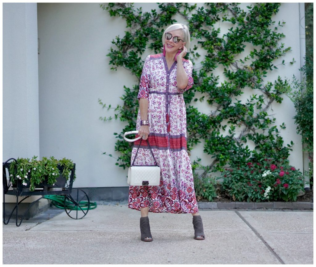 Sheree Frede of the SheSheShow standing in front of trellis wall wearing a maxi red and white floral dress - instagram