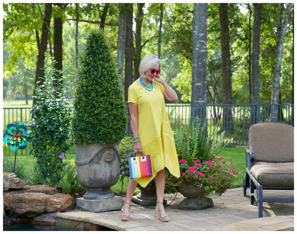 Sheree Frede of the SheShe Show stand in a flower garden wearing a yellow dress