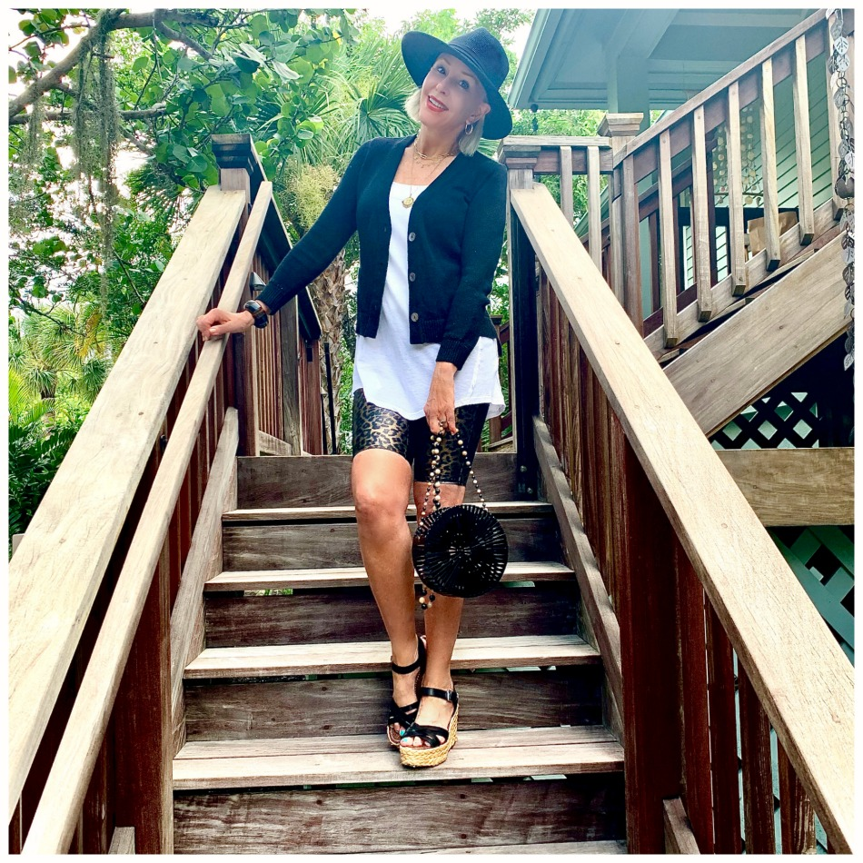 instagram shot of Sheree Frede of the SheShe Show walking up outdoor wooden stairs wearing bike shorts and black cardigan with black hat