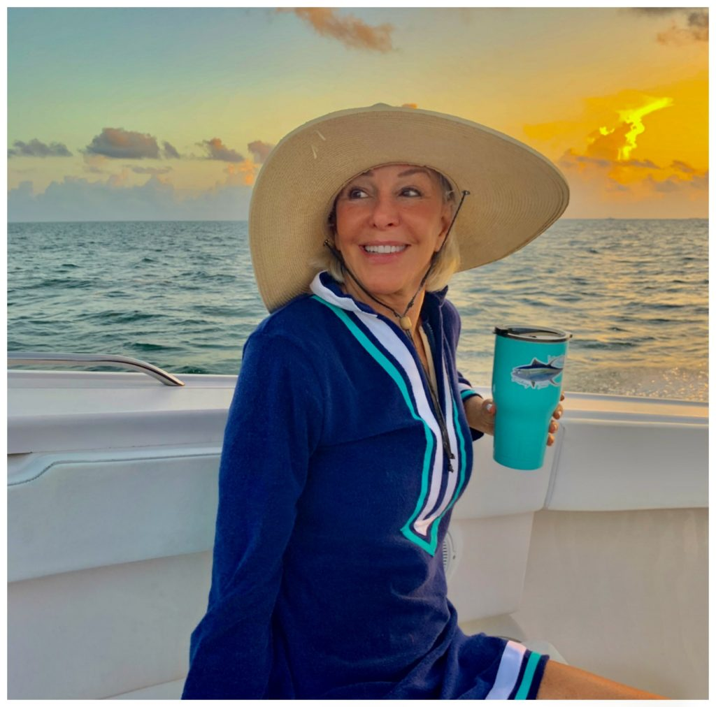 Sheree Frede of the SheShe Show sitting on the bow of a small fishing boat wearing a navy Cabana life swimsuit coverup