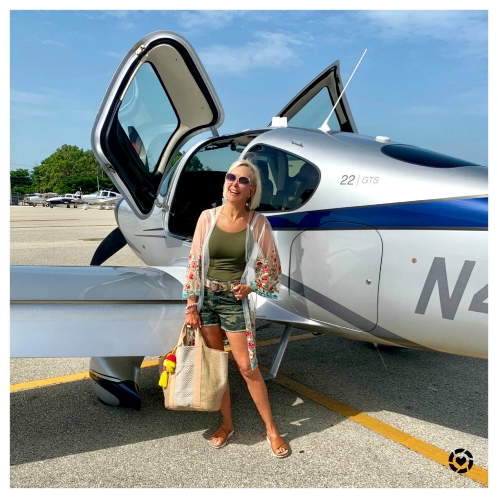Sheree Frede of the SheShe Show standing in front of Cirrus aircraft wearing camo shorts and summer tote bag
