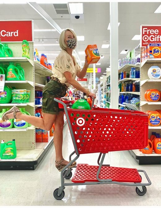 Sheree Frede of the SheShe Show wearing camo shorts riding a grocery cart in the laundry aisle at Target holding Bounty
