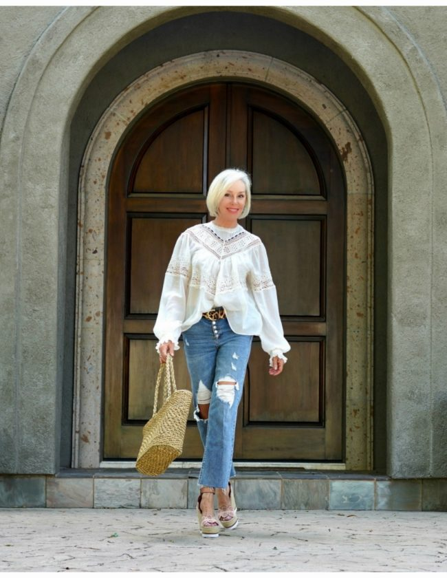 Sheree Frede of the SheShe Show in front of big wood door wearing ripped jeans and an off white victorian top