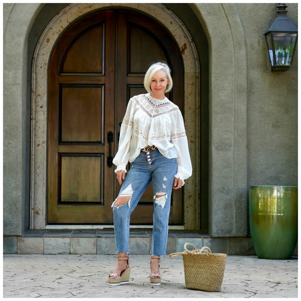 Sheree Frede of the SheShe Show in front of big wood door wearing ripped jeans and an off white victorian top - instagram shot
