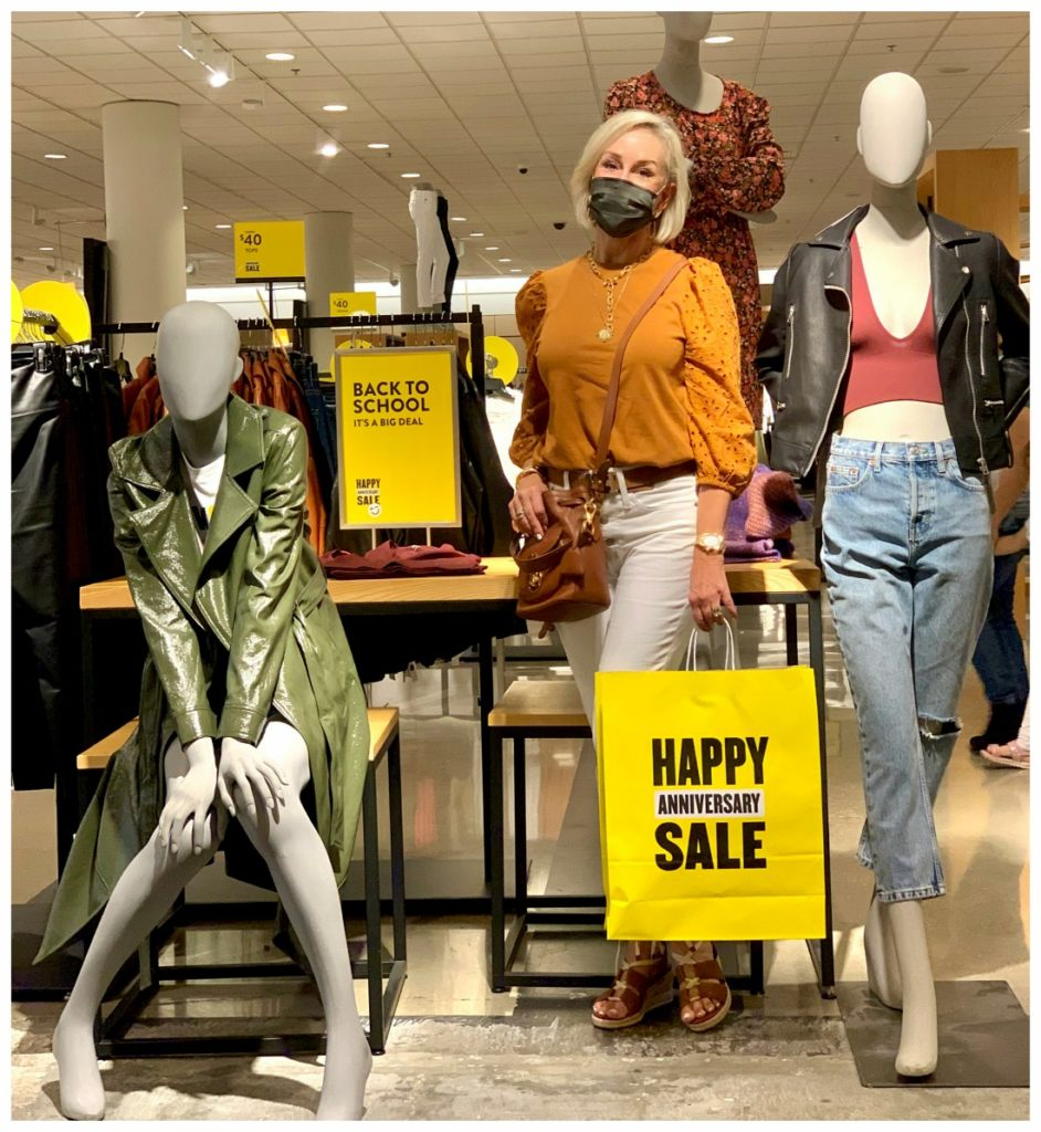 Sheree Frede of the SheShe Show stand on platform with Nordstrom mannequins wearing a burnt orange eyelet top with white jeans