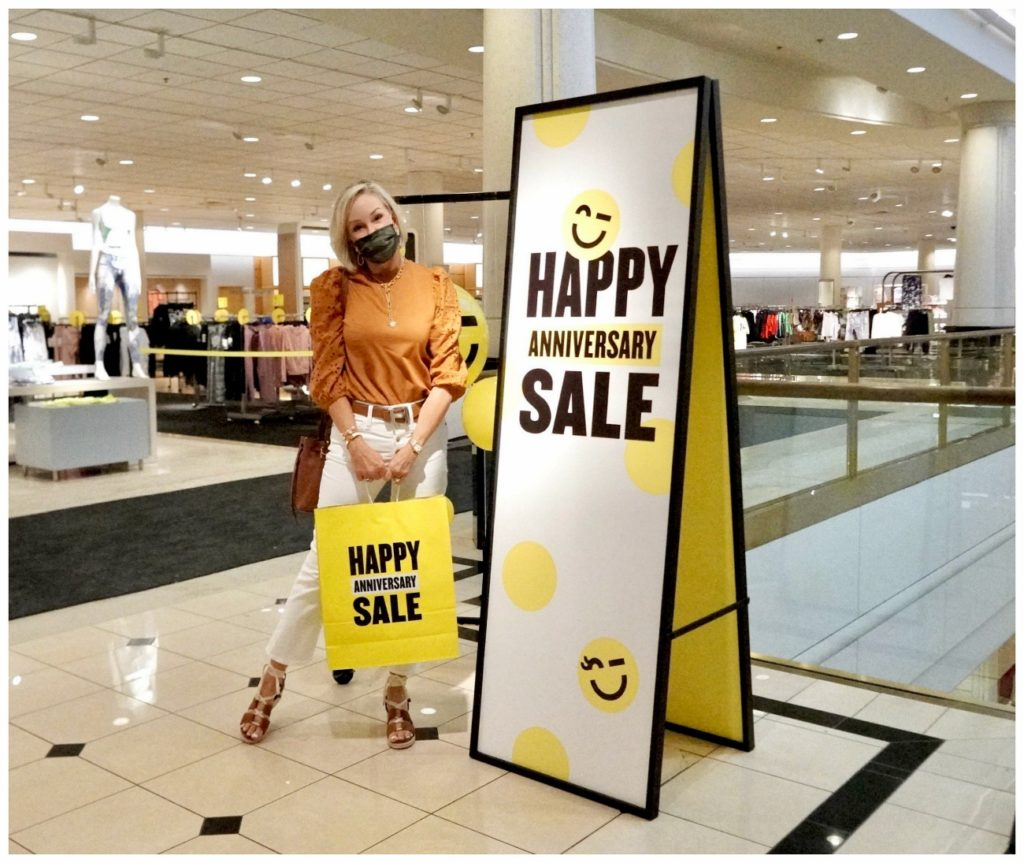 Sheree Frede of the SheShe Show standing by Nordstrom Anniversary Sale sign and holding yellow shopping bag