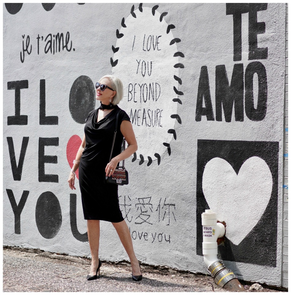 Sheree Frede of the SheShe Show standing in front of mural wall wearing a Chicos black shift dress