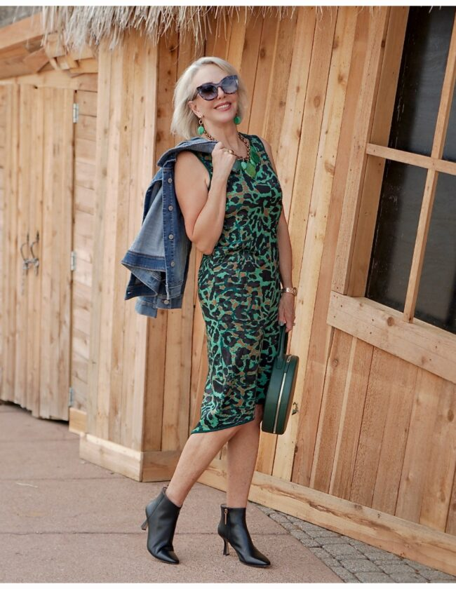 Sheree Frede of the SheShe Show walking in front of a cedar sided house wearing a green leopard print dress with denim jacket
