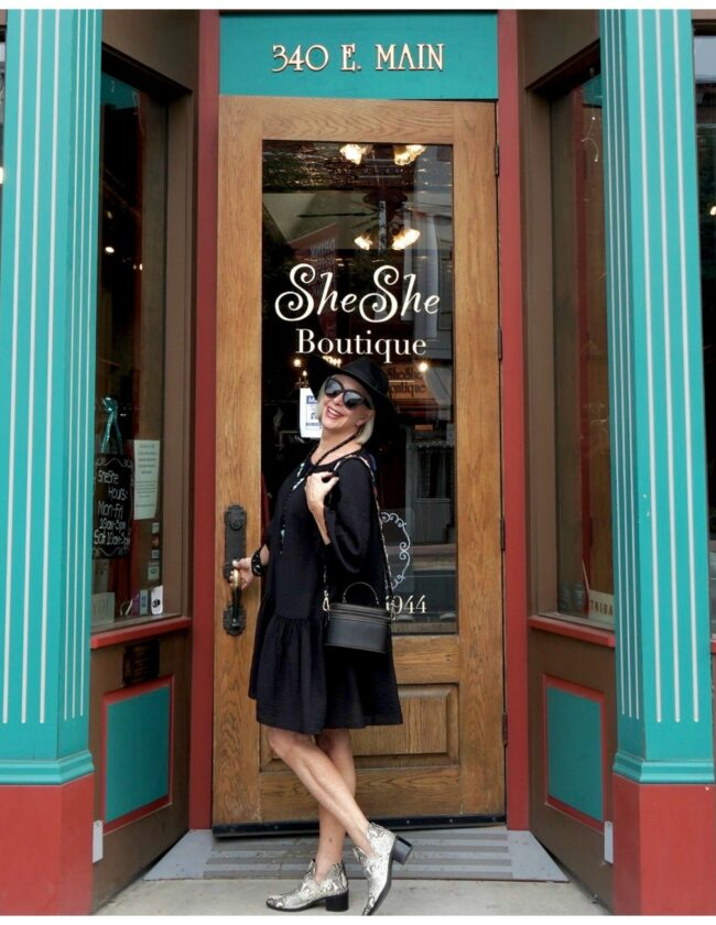 Sheree Frede of the SheSheShow standing in front of a door wearing an above the knee black dress