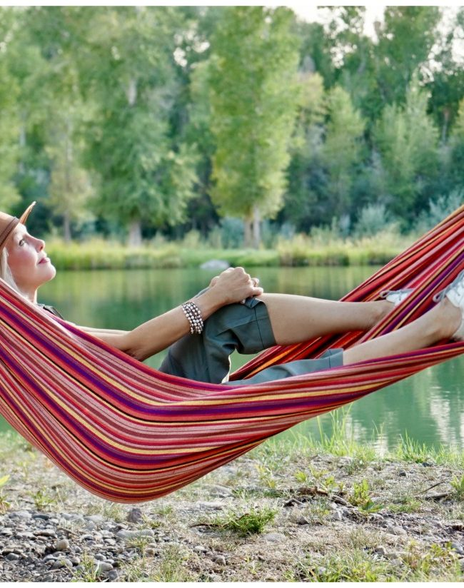 Sheree Frede of the SheShe Show lounging in a hammock by water wearing a brown leather hat and green utility jumpsuit