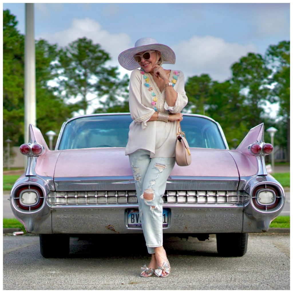 Sheree Frede of the SheShe Show standing by pink cadillac wearing ripped jeans and tassel top