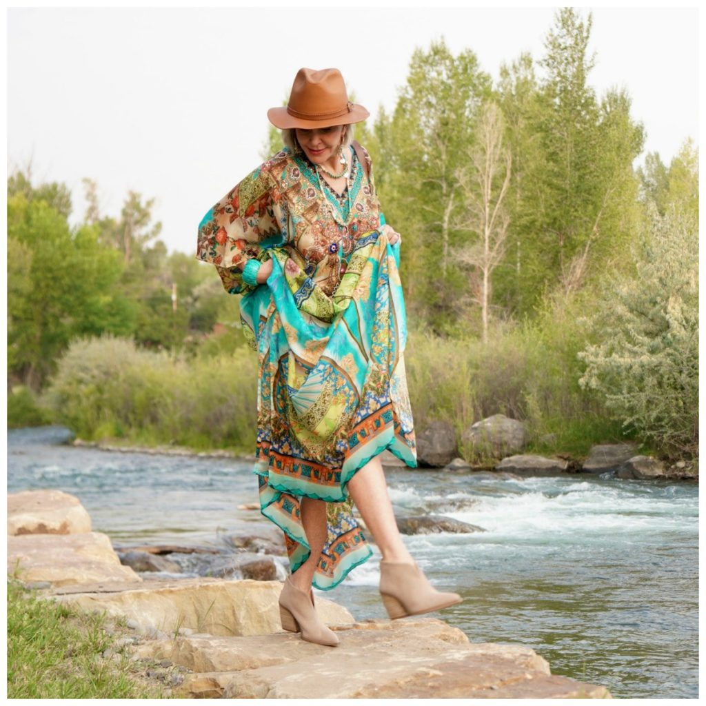 Sheree Frede of the SheShe Show standing by the river wearing a turqoise and rust print kaftan with leather hat.