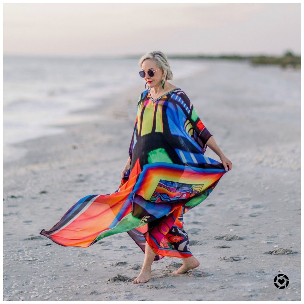 Sheree Frede of the SheShe Show at the. beach wearing a bright multi colored kaftan
