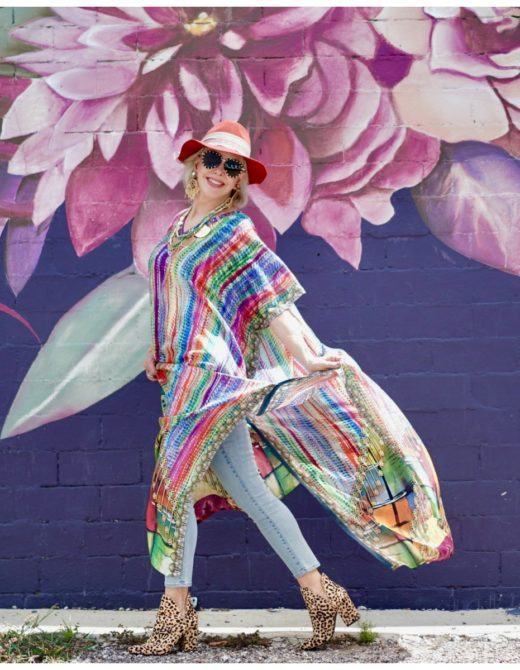 Sheree Frede of the SheShe Show walking in front of purple floral mural wearing a purple, green and orange print silk kaftan with brown leather hat