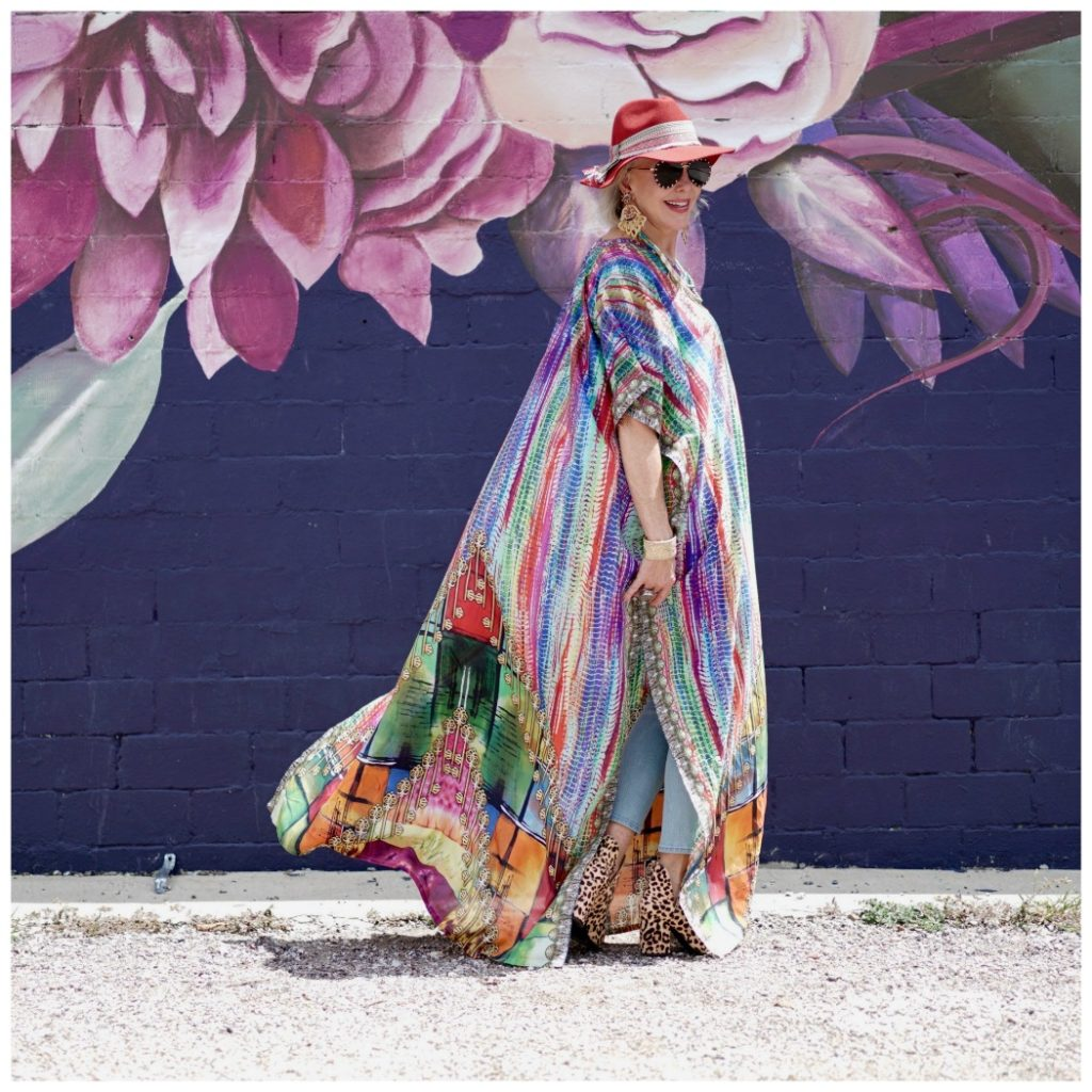 Sheree Frede of the SheShe Show walking in front of purple floral mural wearing a purple, green and orange print silk kaftan