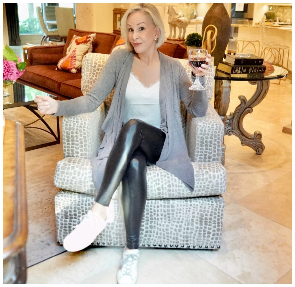 Sheree Frede of the SheShe Show sitting in a chair wearing black leggings and gray cardigan over a white camisole