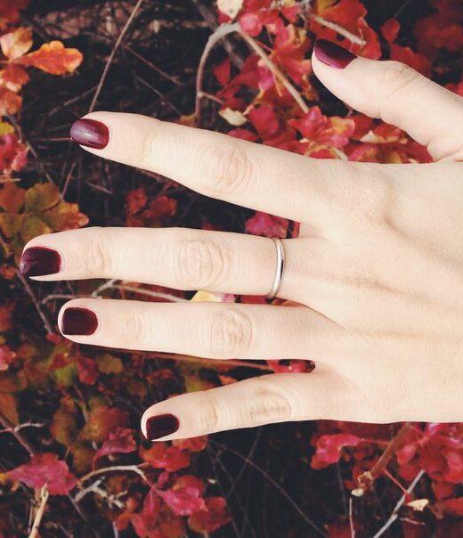 ladies hand wearing wine color nail polish