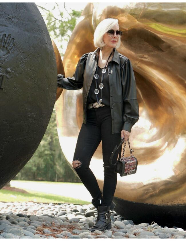 Sheree Frede of the SheShe Show standing in front of an outdoor sculpture wearing a black faux leather shirt and jeans