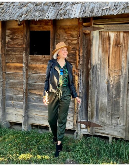 Sheree Frede of the SheShe Show standing in front of old barn wearing green satin jogger pants and leather bomber jacket