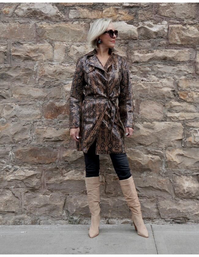 Sheree Frede of the SheShe Show standing in front of rock wall wearing a snakeprint trench coat with tan knee boots