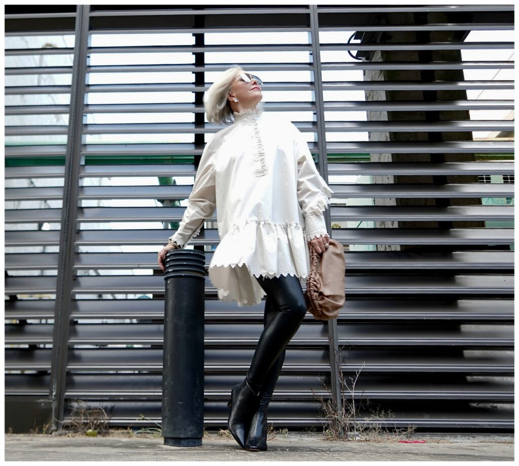 Sheree Frede of the SheShe Show posing in front of grid wearing a white balloon tunic over faux leather leggings