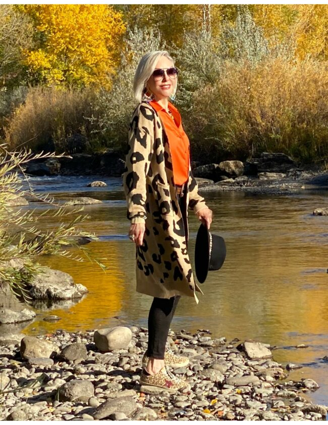 Sheree Frede of the SheShe Show standing on river rocks in the river wearing a lepard print cardigan, orange shirt and black jeans