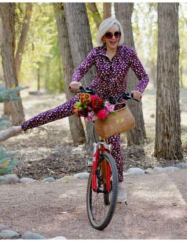 Sheree Frede of the SheShe Show riding a bike wearing a petite floral athleisure set