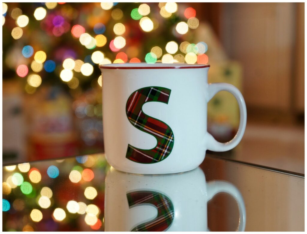 White coffee cup with a large tartan print S on the front with Chritsmas tree in the background.